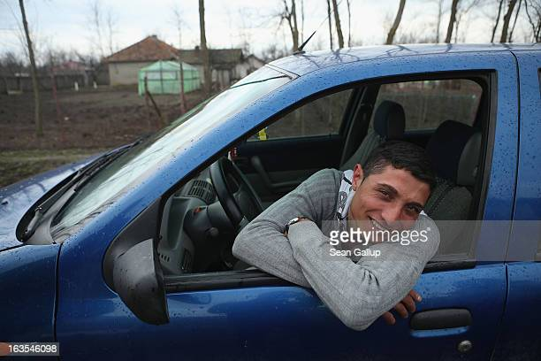 Vasile Nedelcu who is an ethnic Roma smiles from his car on March 11 2013 in Dilga Romania Vasile's mother works in Italy as a senior care nurse...