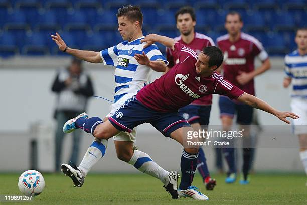 Vasileios Pliatsikas of Duisburg and Mario Gavranovic of Schalke fight for the ball during the Loveparade charity match between MSV Duisburg and FC...