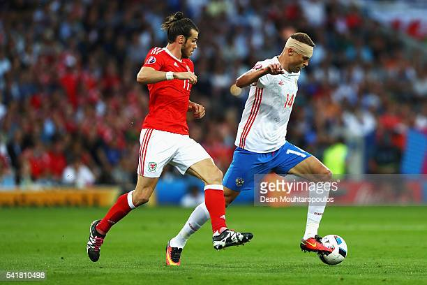 Vasili Berezutski of Russia and Gareth Bale of Wales compete for the ball during the UEFA EURO 2016 Group B match between Russia and Wales at Stadium...