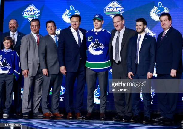 Vasili Podkolzin , tenth overall pick by the Vancouver Canucks, poses for a group photo onstage with team personnel during the first round of the...