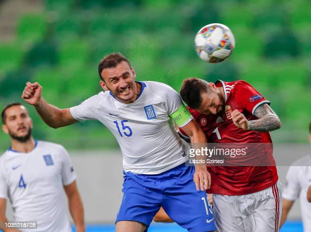 Vasilis Torosidis of Greece battles for the ball in the air with Tamas Kadar of Hungary in front of Kostas Manolas of Greece during the UEFA Nations...