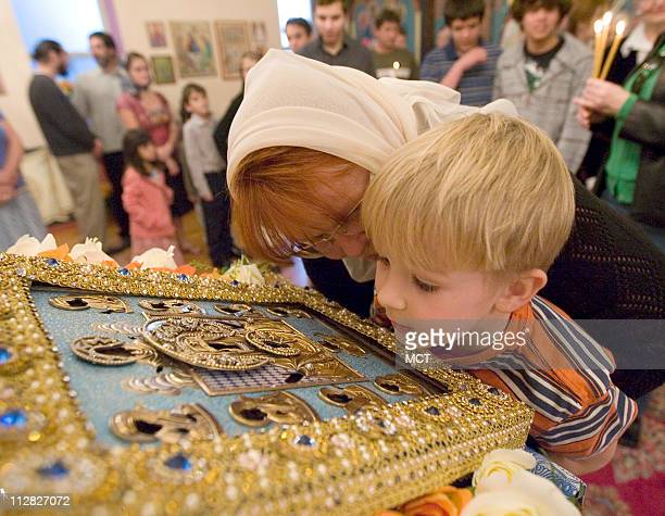 Vasiliy Brooks right is held up by his mother Yelena Brooks to look at the Kursk Root icon after a prayer service lead by Father David Moser at the...