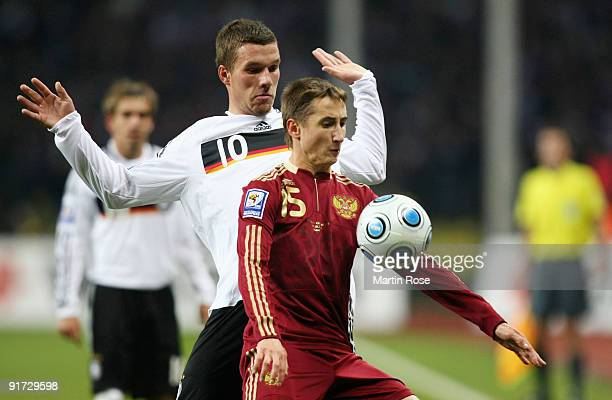 Vasily Brerzutzsky of Russia and Lukas Podolski of Germany battle for the ball during the FIFA 2010 World Cup Group 4 Qualifier match between Russia...