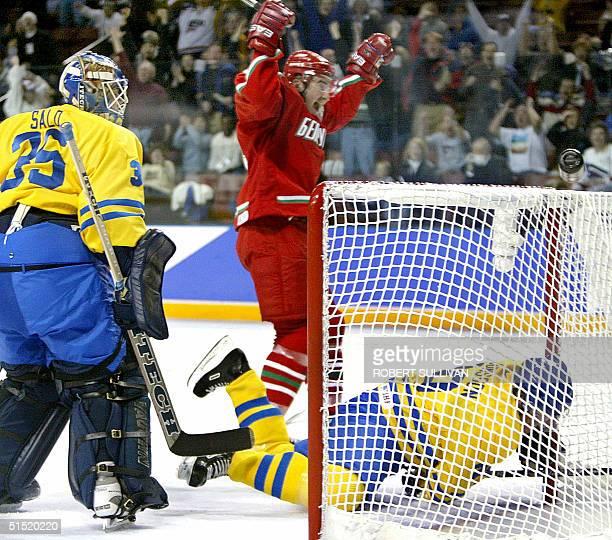 Vasily Pankov of Belarus celebrates the third period goal by teammate Vladimir Kopat before Swedish players, goalie Tommy Salo and Marcus Ragnarsson...