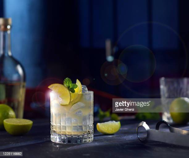 vaso de whisky sour, rodajas de limón y botellas de fondo - cocktail party foto e immagini stock