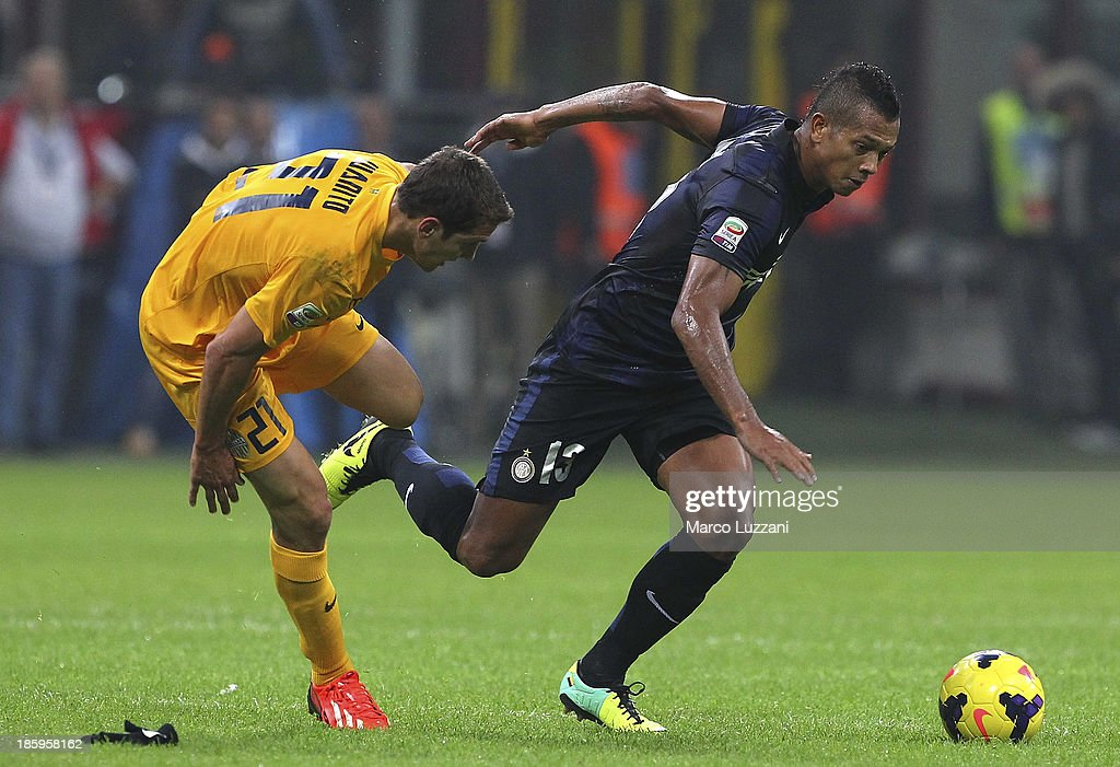 Vasquez Fredy Alejandro Guarin (R) of FC Internazionale Milano competes for the ball with Juanito (L) of Hellas Verona FC during the Serie A match between FC Internazionale Milano and Hellas Verona at Stadio Giuseppe Meazza on October 26, 2013 in Milan, Italy.