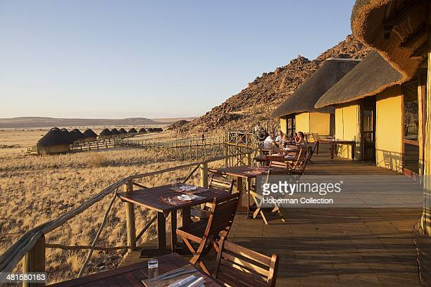 Vast Sunsset Views Of Landscapes And Thatched Camping Site With People Sitting On The Wooden Deck At Sossus Dune Lodge In Namibia