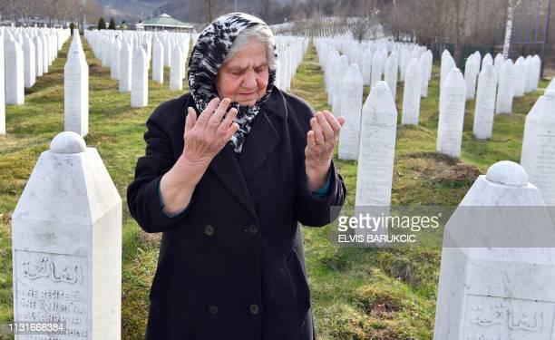 Vasva Smajlovic, a survivor of the Srebrenica massacre in July 1995, prays near tombstones of her relatives, during a visit at the...