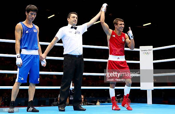 Vasyl Lomachenko of Ukraine celebrates as the referee announces him the winner over Soonchul Han of Korea during the Men's Light Boxing final bout on...