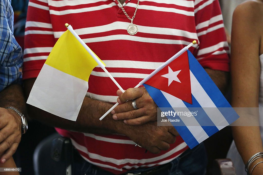 Vatican and Cuban flags are held as during a mass lead by Pope Francis at the Cathedral of Our Lady of the Assumption on September 22, 2015 in Santiago de Cuba, Cuba. Pope Francis left for the United States after spending four days in Cuba.