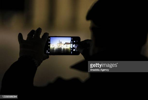A reporter uses his smartphone to take a picture to St Peter's Square before the start of the celebration of the Via Crucis torchlight procession...