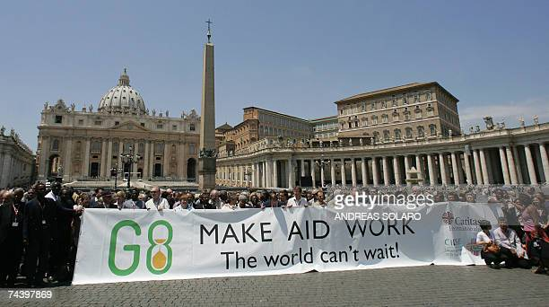 Caritas Internationalis delegates unveils a giant banner reading 'Make Aid Work' to call on the Group of Eight industrialised countries to do more to...