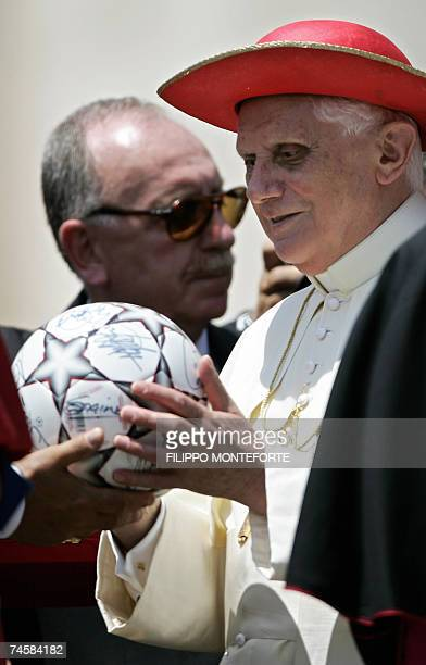 Pope Benedict XVI holds a soccer ball received as a gift after his weekly general audience in Saint Peter's Square at the Vatican 13 June 2007 AFP...
