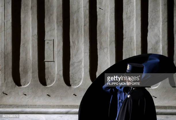 Vatican Gendarme adjusts his cloak as Pope Francis celebrates the holy Mass for the families in St.Peter's Basilica at the Vatican, on December 27,...