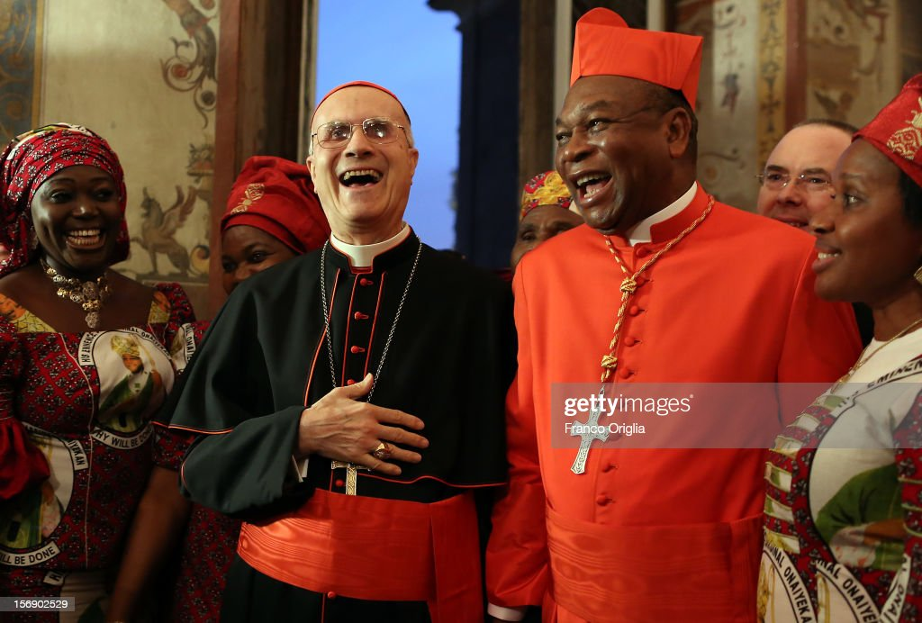 Vatican secretary of State cardinal Tarcisio Bertone (L) poses with newly appointed cardinal John Olorunfemi Onaiyekan (R), archbishop of Abuja Nigeria, and his diocesans during the courtesy visits at the Sala Regia Hall at the end of the concistory held by Pope Benedict XVI on November 24, 2012 in Vatican City, Vatican. The Pontiff installed 6 new cardinals during the ceremony, who will be responsible for choosing his successor.