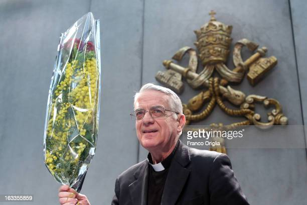 Vatican spokesman father Federico Lombardi holds a bunch of mimosa, a flower marking the International Women's Day on March 8, as he arrives at the...