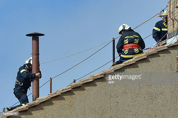 Vatican's firefighters setup the chimney on the roof of the Sistine chapel ahead of the cardinals conclave on March 9, 2013. Vatican workers made...