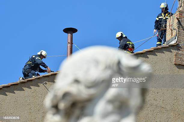 Vatican's firefighters setup the chimney on the roof of the Sistine chapel past the statue of St Paul ahead of the cardinals conclave on March 9,...