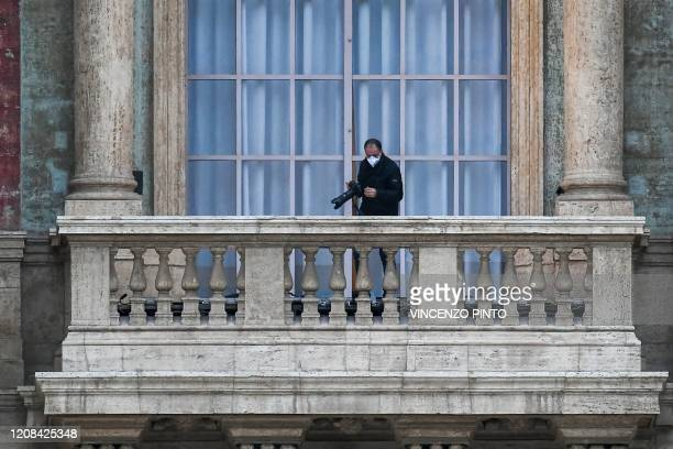 A Vatican's photographer wearing a face mask stands on a balcony of St Peter's basilica prior to the Pope presiding over a moment of prayer on the...