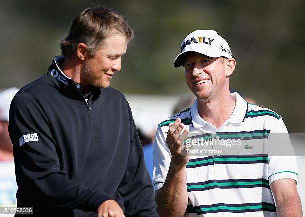 Vaughn Taylor and Matt Jones of Australia talk after completing their round on the 18th green during the final round of the AT&T Pebble Beach...