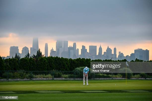 Vaughn Taylor putts on the practice range as the sun rises beyond the Manhattan skyline during the first round of THE NORTHERN TRUST, the first event...