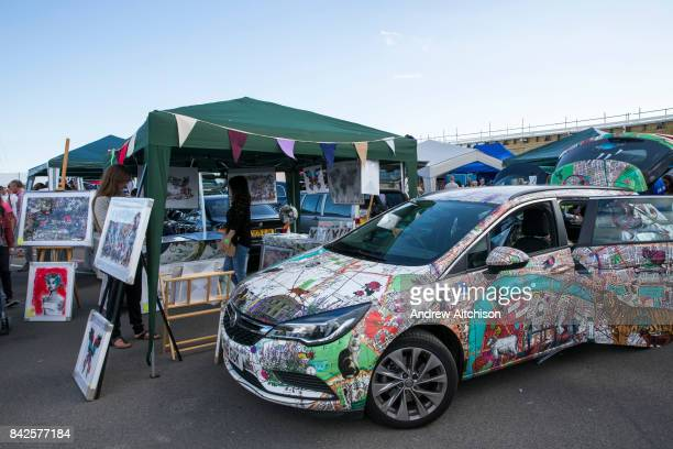 A Vauxhall car decorated by the Artist Kristjana S Williams parked next to her stall at the 2017 Art Car Boot Fair Folkestone Kent
