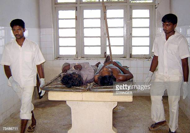 Sri Lankan hospital workers leave the morgue after placing for forensic tests the bulletriddled bodies of two Tamil men shot dead by unidentified men...