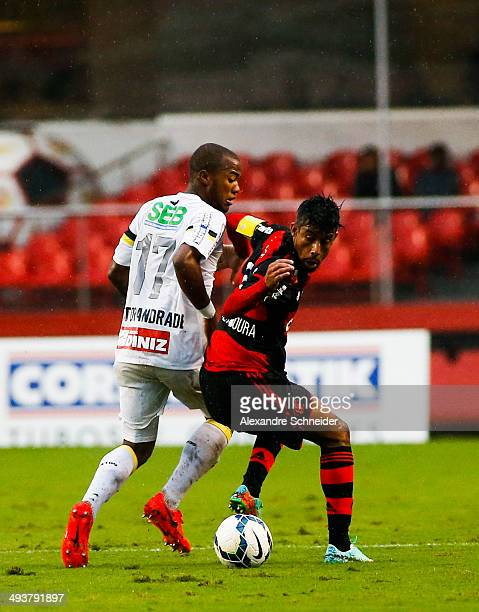 Vctor Andrade of Santos battles for the ball with Leo Moura of Flamengo during the match between Santos and Flamengo for the Brazilian Series A 2014...