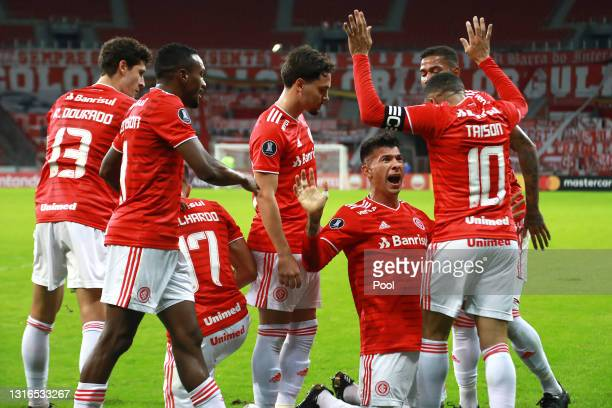 Víctor Cuesta of Internacional celebrates with teammates after scoring the first goal of his team during a match between Internacional and Olimpia as...