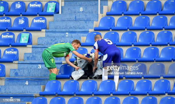 Víctor Laguardia of Deportivo Alaves and iDavid Zurutuza of Real Sociedad lay out flowers in the stands ahead of the Liga match between Deportivo...