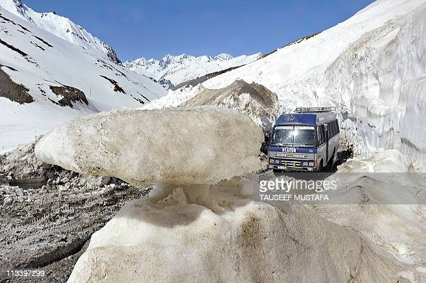 A vechile is driven on a mountainous road after the SrinagarLeh highway was opened to traffic in Zojila about 108 km east of Srinagar on May 2 2011...