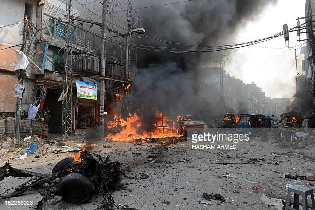Vechiles and shops burn at the site of a bomb explosion in the busy Kissa Khwani market in Peshawar on September 29 2013 A bomb explosion killed at...