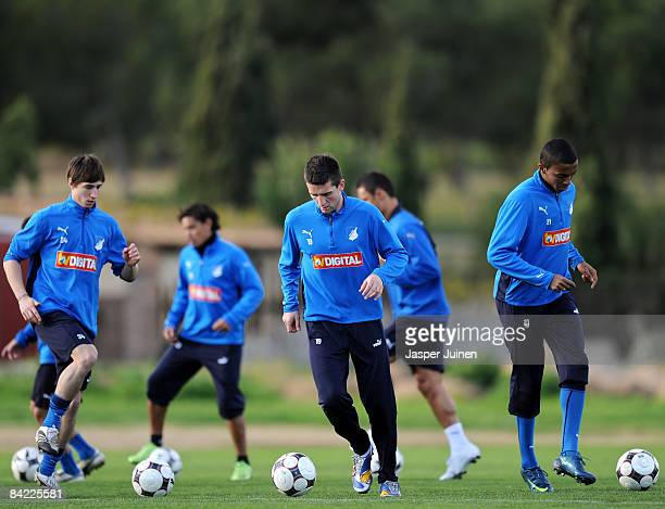 Vedad Ibisevic of 1899 Hoffenheim jogs with the ball flanked by his teammate Luiz Gustavo Dias during day one of their team's training camp on...