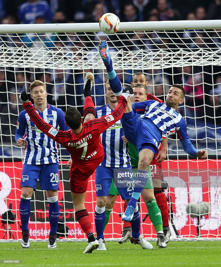 Vedad Ibisevic (R) of Berlin battles for the ball with Chicharito (L) of Leverkuasen during the Bundesliga match between Hertha BSC and Bayer Leverkusen at Olympiastadion on December 5, 2015 in Berlin, Germany.