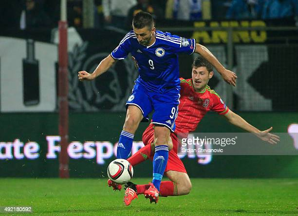 Vedad Ibisevic of Bosnia is challenged by Joe Allen during the Euro 2016 qualifying football match between Bosnia and Herzegovina and Wales at the...