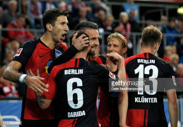 Vedad Ibisevic of Hertha BSC celebrates with teammates after scoring his team's second goal during the Bundesliga match between 1 FC Koeln and Hertha...