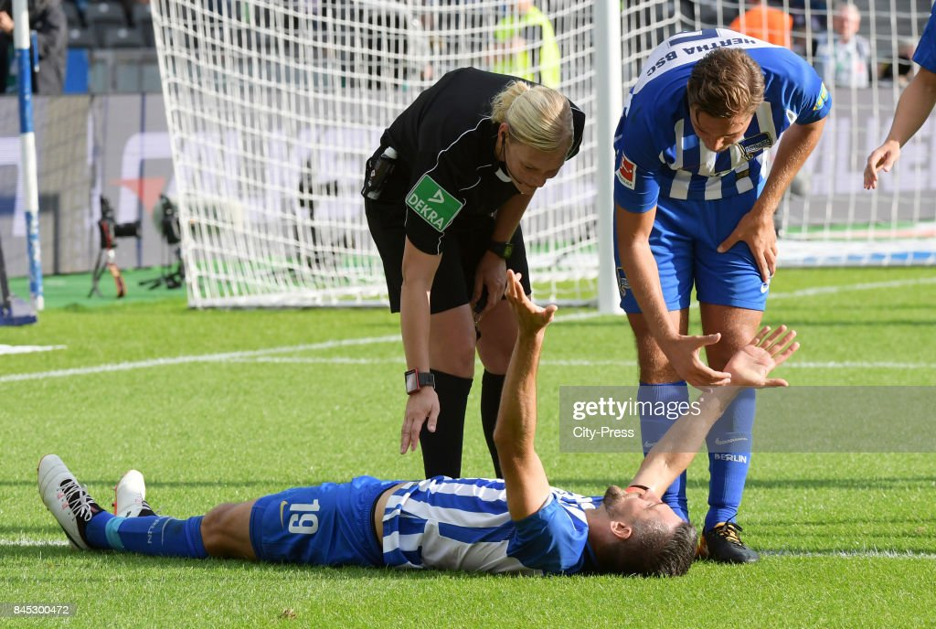 Vedad Ibisevic of Hertha BSC, Match referee Bibiana Steinhaus and Niklas Stark of Hertha BSC during the game between Hertha BSC and Werder Bremen on September 10, 2017 in Berlin, Germany.