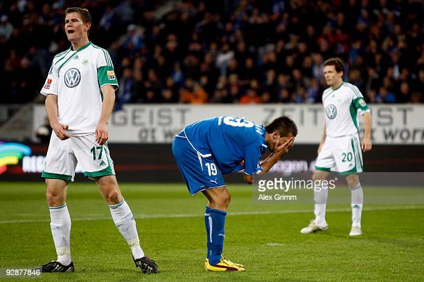 Vedad Ibisevic of Hoffenheim reacts as he stands between Alexander Madlung and Sascha Riether of Wolfsburg during the Bundesliga match between 1899...