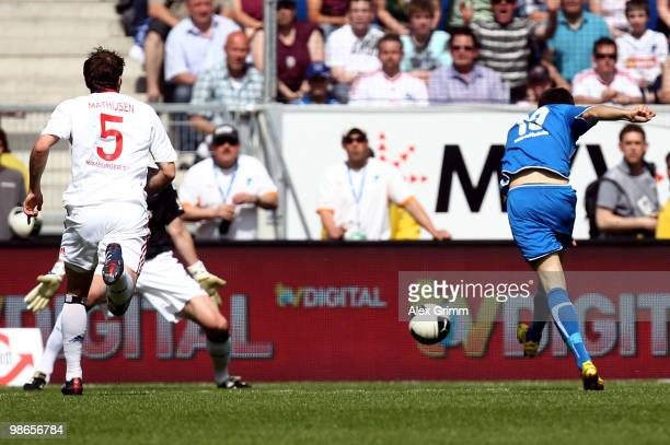 Vedad Ibisevic of Hoffenheim scores his team's first goal against Joris Mathijsen and goalkeeper Frank Rost of Hamburg during the Bundesliga match...
