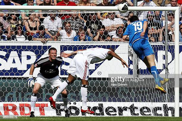 Vedad Ibisevic of Hoffenheim scores his team's second goal against Jerome Boateng and goalkeeper Frank Rost of Hamburg during the Bundesliga match...