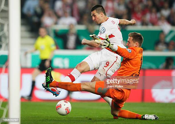 Vedad Ibisevic of Stuttgart and goalkeeper Oliver Baumann of Freiburg compete for the ball during the DFB Cup Semi Final match between VfB Stuttgart...