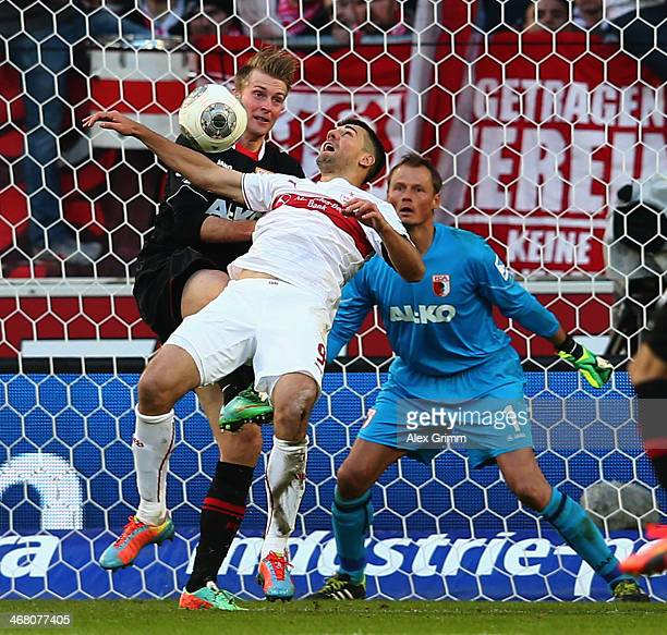 Vedad Ibisevic of Stuttgart is challenged by Jan-Ingwer Callsen-Bracker and goalkeeper Alexander Manninger of Augsburg during the Bundesliga match...