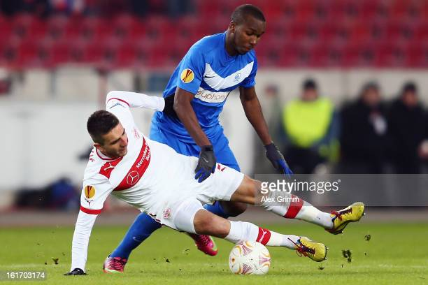 Vedad Ibisevic of Stuttgart is challenged by Khaleem Hyland of Genk during the UEFA Europa League Round of 32 first leg match between VfB Stuttgart...