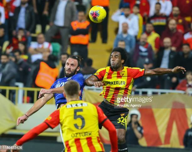 Vedat Muriqi of Fenerbahce and Cameron Jerome of Goztepe vie for the ball during the Turkish Super Lig soccer match between Goztepe and Fenerbahce at...