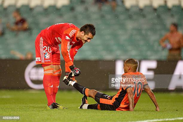 Vedran Janjetovic of Sydney helps Henrique Andrade Silva of the Roar with an injury during the round 12 ALeague match between Sydney FC and Brisbane...