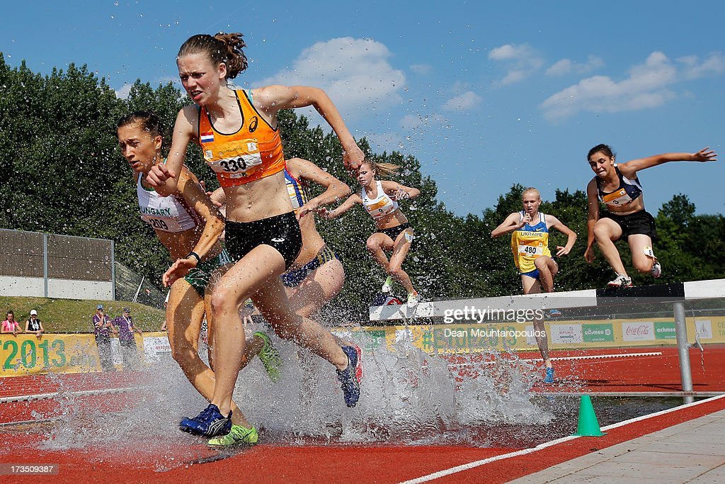 Veerle Bakker (Orange top) of Netherlands and Lili Anna Toth (white top) of Hungary compete in the 2000m Girls steeple race during the European Youth Olympic Festival held at the Athletics Track Maarschalkersweerd on July 15, 2013 in Utrecht, Netherlands.