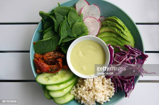 Vegan breakfast of pearl couscous and raw vegetables: cucumber, sundried-tomatoes, baby spinach, radish, avocado, and red cabbage with aioli