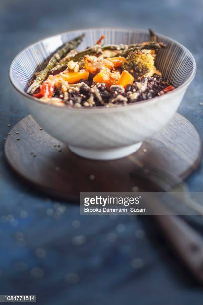 a vegan buddha bowl with black rice, toasted vegetables and tahini sauce - black rice stock pictures, royalty-free photos & images