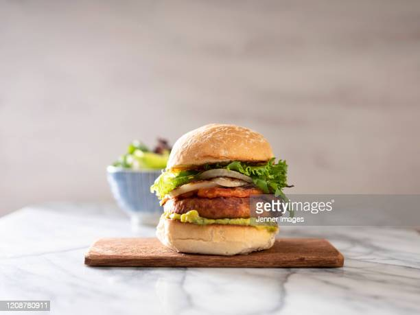 vegan burger on a chopping board. bowl of salad in the background. - vegetarian food stock pictures, royalty-free photos & images