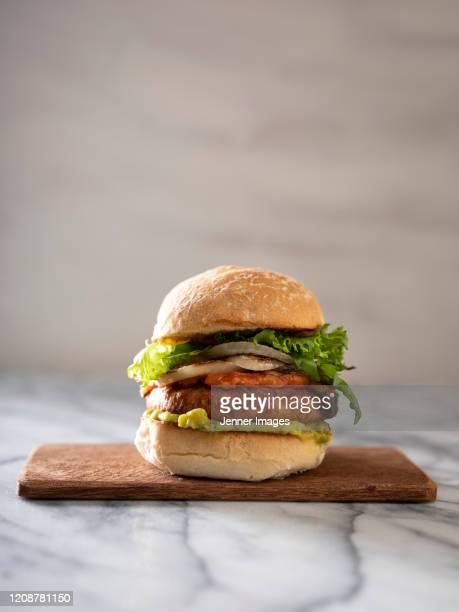 vegan burger on a chopping board. - meat substitute stock pictures, royalty-free photos & images